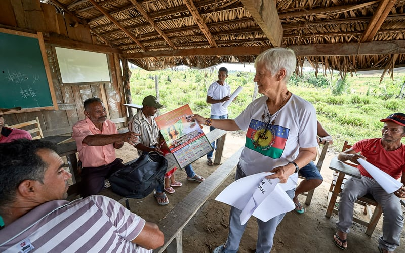 """U.S. Sister Kathryn """"Katy"""" Webster, a member of the Sisters of Notre Dame de Namur from the United States, hands out a calendar that promotes the Synod of Bishops on the Amazon to farmers in the countryside near Anapu, in Brazil's northern Para state, in this April 2019 file photo. (CNS photo/Paul Jeffrey)"""