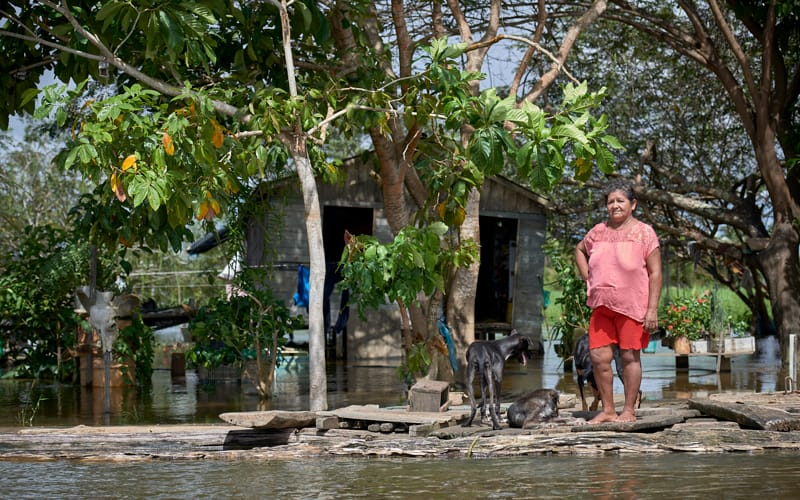 "Juscelina Silva Batista, 54, stands in front of her house in the middle of the Amazon River near Santarem, Brazil, April 11, 2019. The Vatican released Pope Francis' postsynodal apostolic exhortation, ""Querida Amazonia"" (Beloved Amazonia), Feb. 12, 2020. (CNS Photo/Paul Jeffrey)"