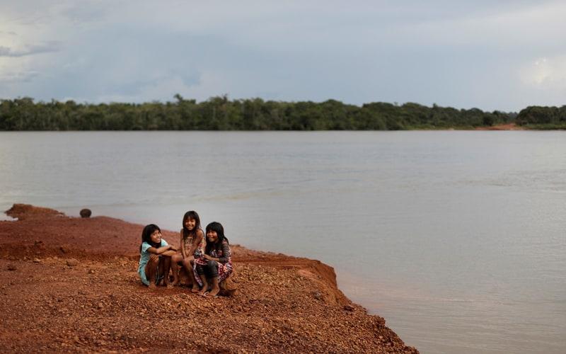Indigenous children sit on the banks of the Xingu River in Brazil's Xingu Indigenous Park Jan. 15, 2020. (CNS photo/Ricardo Moraes, Reuters)