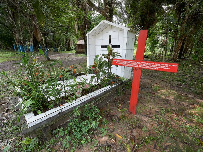 A red cross stands beside the grave of U.S.-born Sister Dorothy Stang in Anapu, Brazil. Sister Stang was assassinated in 2005. The red cross beside her grave bears the names of 16 local rights activists murdered since her killing. Church activists say the killings continue, and by April 2019 they were about to erect a second red cross with even more names. (CNS Photo/Paul Jeffrey)