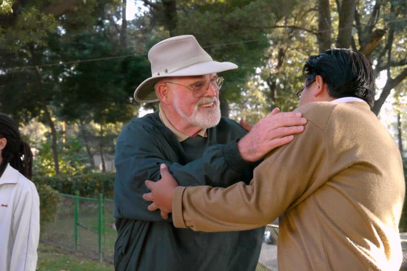 Father Henehan greets a participant of the Maryknoll Mission Center in Latin America. (Sean Sprague / Bolivia)