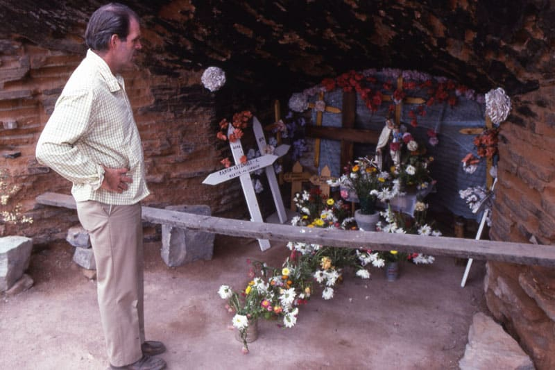 Father Henehan looks at the crosses and flowers placed at the site of a mass grave of the disappeared in Lonquen, Chile, 1980. (Maryknoll Mission Archives)