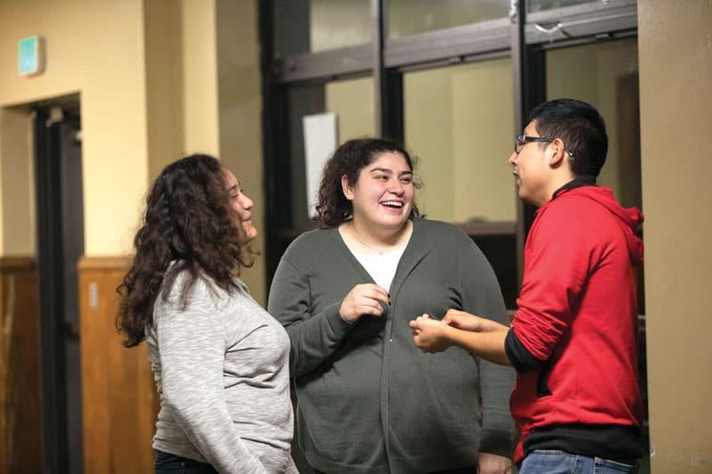 Fatima Carrillo (center), a leader of Peace Warriors, talks with teenagers on a Friday. (Octavio Durán / Illinois)