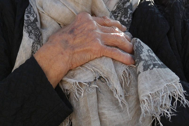 Pandemic Isolation: An elderly woman's hands are seen in this photo. Many residents of nursing facilities are now isolated because of COVID-19. (CNS photo/Paul Haring)