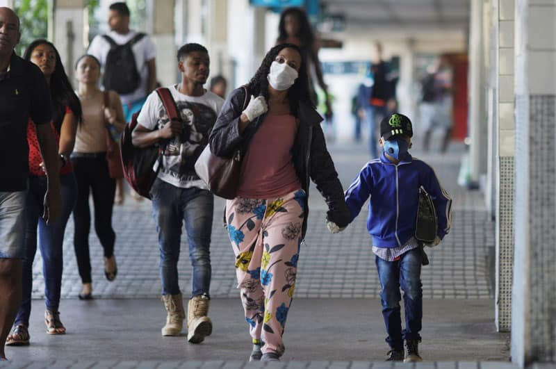 Latin American governments weigh pandemic shutdown vs. economic hardship: A woman and child wearing protective masks walk through Central do Brasil train station in Rio de Janeiro during the coronavirus pandemic March 24, 2020. (CNS photo/Ricardo Moraes, Reuters)