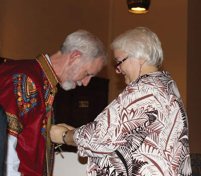 Marj Humphrey, director of missions for the Maryknoll Lay Missioners, presents a mission cross to Greg Garrity at the group's sending ceremony for new missioners in December 2019. (Deborah Northern/U.S.)
