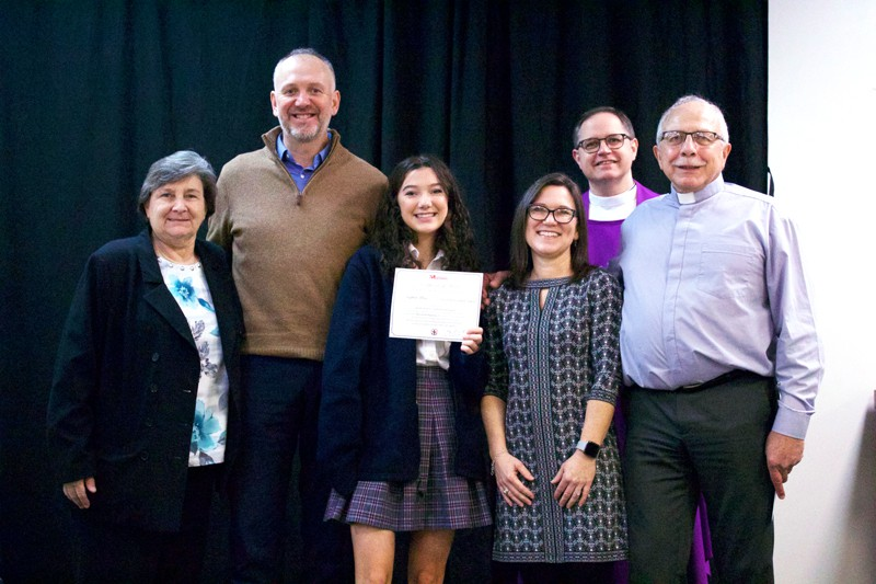 Sophia Allen, 12th-grader at Sacred Heart Catholic School in Anniston, Ala., holds her first-place award for Division II of Maryknoll Essay Contest 2019, with (l. to r.) principal Frances Shipp, dad Jim, mom Anna, pastor Father John McDonald, Maryknoll Father Douglas May. (Emily Harrell/U.S.)