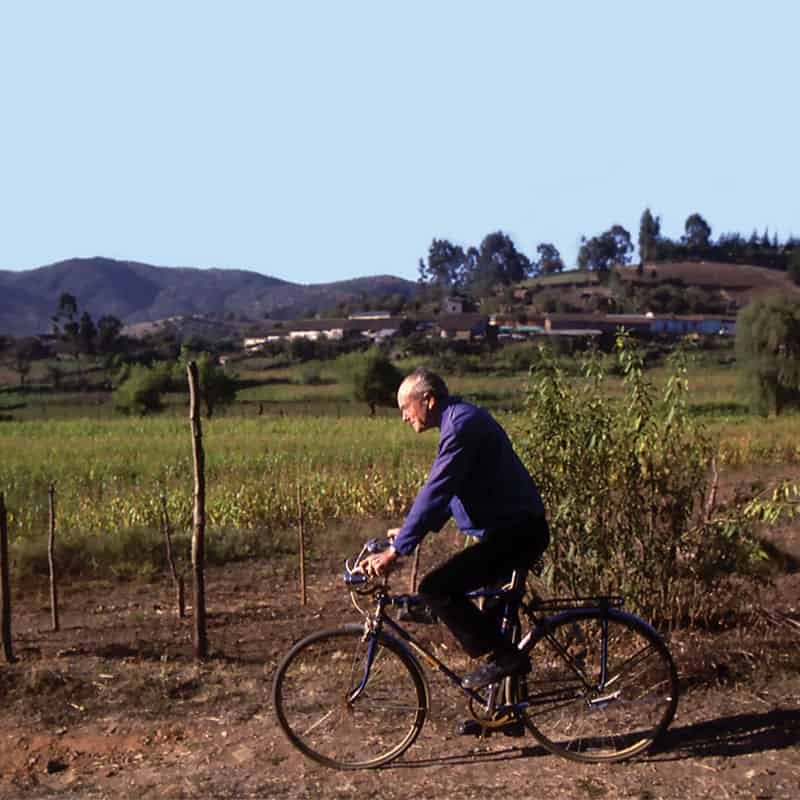 """Riding over dirt roads to visit parishioners in remote areas earned Father Joseph Cappel the moniker """"Bicycle Priest."""" (Maryknoll Mission Archives/Chile)"""