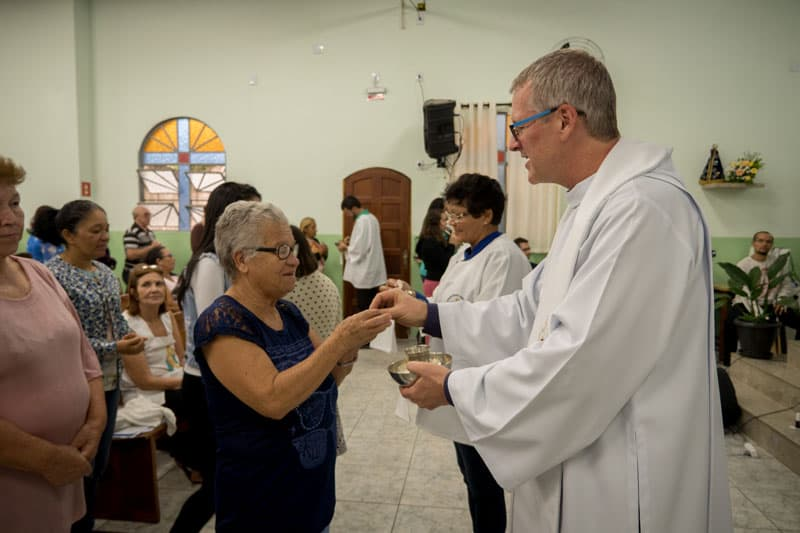 Before the quarantine and trauma of COVID-19, Father Dennis Moorman distributed Holy Communion at Mass at St. Joseph Church in Perus, Sao Paulo, Brazil. (Nile Sprague/Brazil)