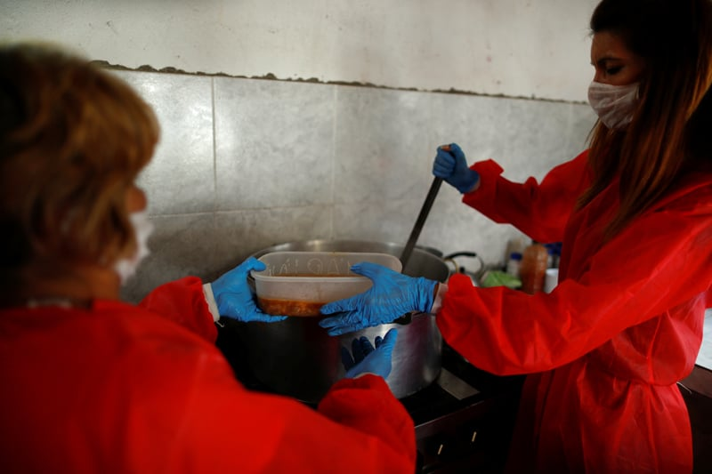 Volunteers wearing protective masks serve stew at a soup kitchen in Buenos Aires, Argentina, March 26, 2020. (CNS photo/Agustin Marcarian, Reuters)