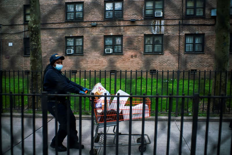 Pandemic highlights disparities in ethnic communities: A woman in New York City pushes her cart of donated food April 15, 2020, during the coronavirus pandemic. (CNS photo/Eduardo Munoz, Reuters)