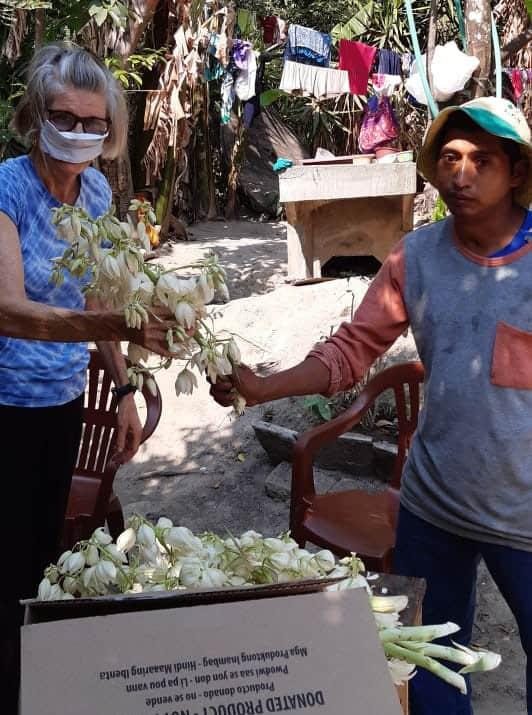 delivering food during El Salvador quarantine: As a thank-you, David Luna gives Ann some Flor de Izote, the national flower of El Salvador, which grows on giant yucca. (Courtesy of Ann Greig/El Salvador)
