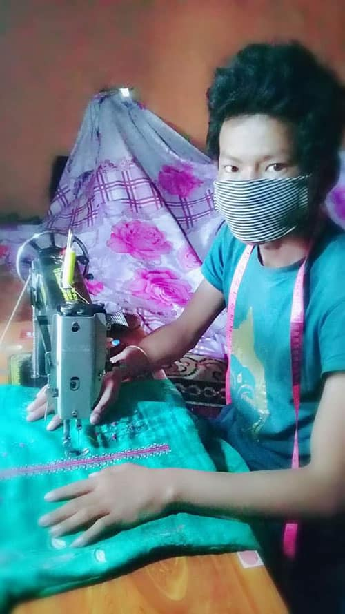 A young villager who graduated from the Maryknoll-sponsored Sewing and Cutting Training Program for Persons with Disabilities in Nepal wears a homemade face mask while working on another garment during the COVID-19 pandemic. (Courtesy of Joseph Thaler/Nepal)