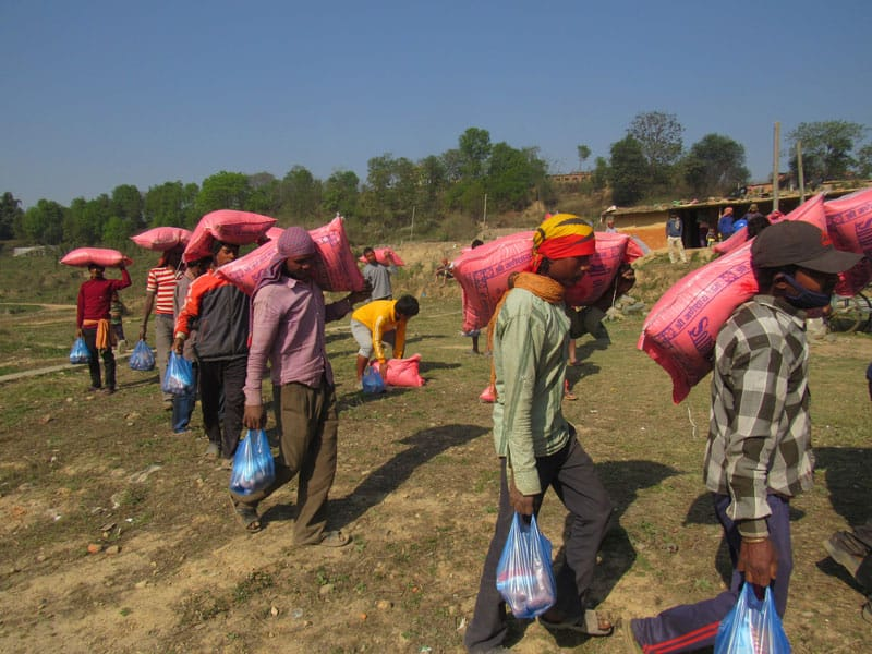 Brick factory workers living on the outskirts of Kathmandu, the capital of Nepal, collect food supplies donated by the Maryknoll Fathers and Brothers in response to the COVID-19 pandemic. (Courtesy of Joseph Thaler/Nepal)