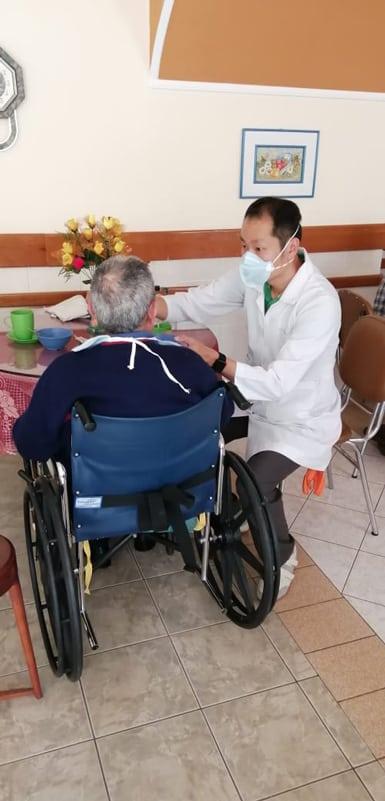 Matthew Sim, a Maryknoll seminarian from Singapore, feeds a resident at a senior home in Cochabamba, Bolivia.