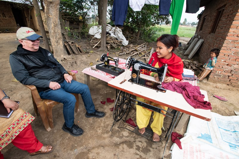 Maryknoll Father Joseph Thaler visits with Reena Tharu, a graduate of the yearlong residential Sewing and Cutting Training Program for Persons with Disabilities in Bardiya District, Nepal, outside her home in Khairapur prior to the coronavirus outbreak. Such graduates are now sewing face masks for people in their villages during the COVID-19 pandemic. (Gregg Brekke/Nepal)