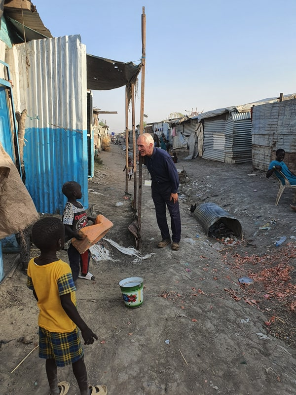 Father Bassano greets children at a a displaced persons camp in South Sudan. During the COVID-19 lockdown, large gatherings or church activities have been restricted. (Courtesy of Michael Bassano/South Sudan)