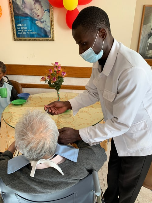 Wearing a face mask Charles Ogony, a Maryknoll seminarian from Kenya, feeds a resident at a senior home run by the Little Sisters of the Abandoned Elderly in Cochabamba, Bolivia. Ogony and fellow seminarian Matthew Sim helped out at the home after volunteers were withdrawn due to the Covid-19 pandemic. (Matthew Sim/Bolivia)