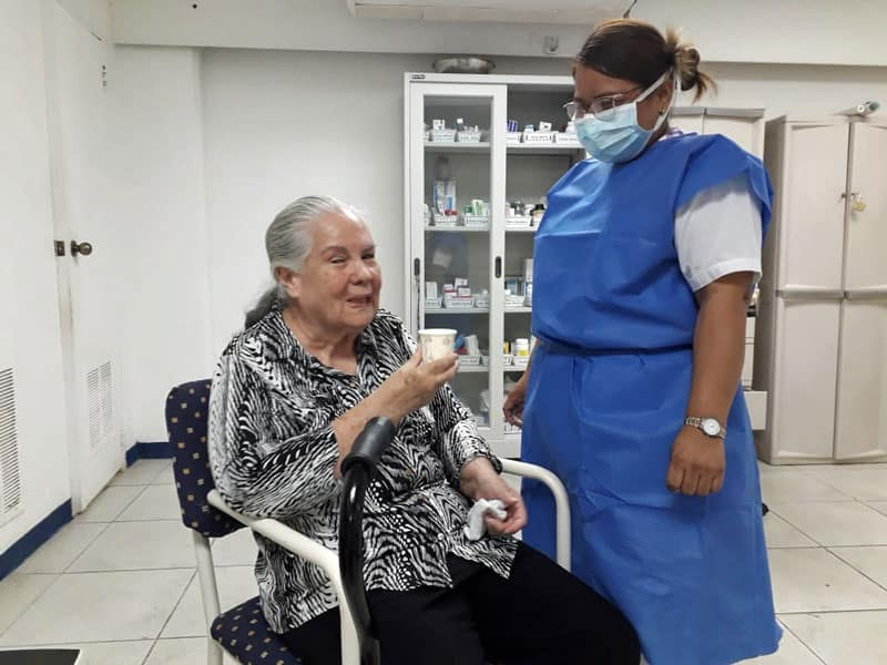 Gloria Paz Rodriguez, a longtime resident of Fundación Nueva Vida, receives medication from one of the elder care residence's aides. (Courtesy of Geraldine Brake/Panama)
