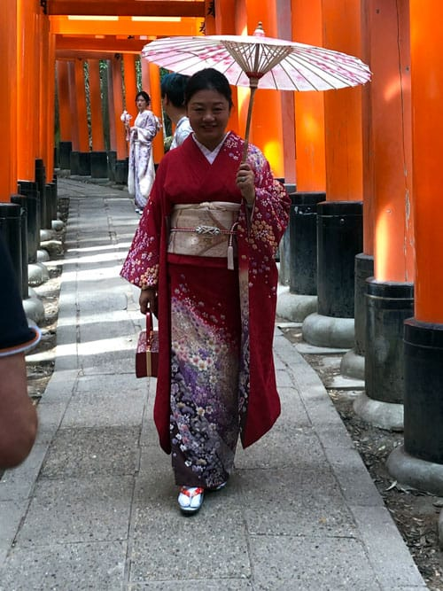 In 2019, before COVID-19 hit Japan, a Japanese woman stands outside the vermilion gates of Fushimi Inari-Taisha shrine in Kyoto. (Peter Saunders/Japan)