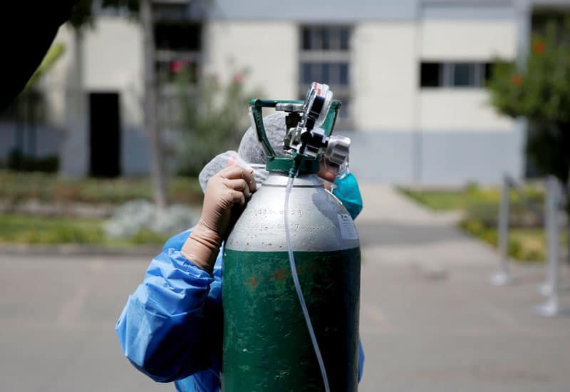 A nurse adjusts an oxygen tank next to a tent for COVID-19 patients in the parking lot of a hospital in Lima, Peru, April 16, 2020. As coronavirus cases surge in Peru's two largest Amazonian cities, Iquitos and Pucallpa, Catholic leaders are struggling to find ways to provide the sick with the most basic health need, life-sustaining oxygen. (CNS photo/Sebastian Castaneda, Reuters)