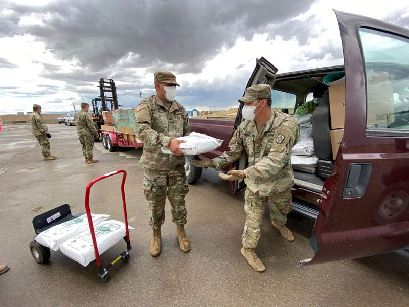 Members of the New Mexico Army National Guard in Standing Rock, N.M., put bags of flour into a truck as they assist with food distribution throughout the Navajo reservation May 11, 2020, amid the coronavirus pandemic. (CNS photo/Donovan Quintero, Reuters)