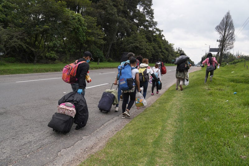 Venezuelan migrants carrying their belongings walk along a highway leading out of Bogota, Colombia, in early April, during the COVID-19 pandemic. The migrants had no money for bus fare and were making a 400-mile trek toward the Venezuelan border. (CNS photo/Manuel Rueda)