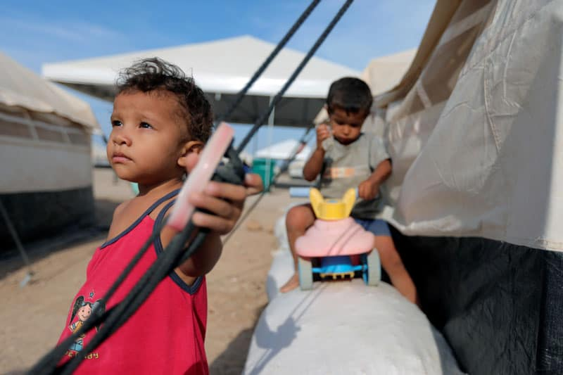 Venezuelan migrant children are seen in early May next to a tent at a camp in Maicao, Colombia, during the COVID-19 pandemic. (CNS photo/Luisa Gonzalez, Reuters)