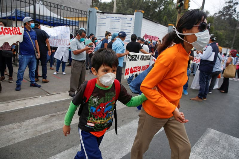 A woman and a child are seen in front of health care workers protesting the lack of proper medical supplies in early May outside a hospital in Lima, Peru, during the COVID-19 pandemic. (CNS photo/Sebastian Castaneda, Reuters)