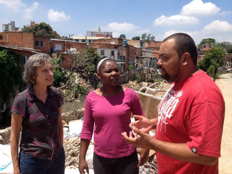 Brazil environmental impact: Joanne Blaney (left), with Maryknoll Sister Armeline Sidoine and José Silva, an educator and community leader, in the favela of Capão Redondo, which suffers from both drought and flooding and has high levels of urban violence and environmental degradation (Photo courtesy of Maryknoll Lay Missioners).