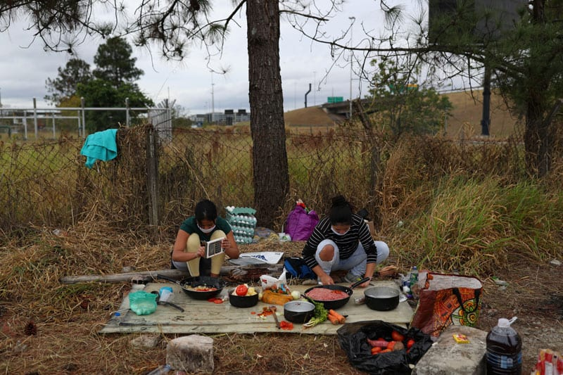 As Latin America Becomes Center of Pandemic, Church Confronts Hunger: Isabella Ceballo, 19, and Yulieth Morales, 23, cook near Brazil's Guarulhos International Airport outside Sao Paulo May 24, 2020. They were part of a group of about 200 Colombians living temporarily near the airport due to restrictions enforced during the COVID-19 pandemic. (CNS photo/Amanda Perobelli, Reuters)