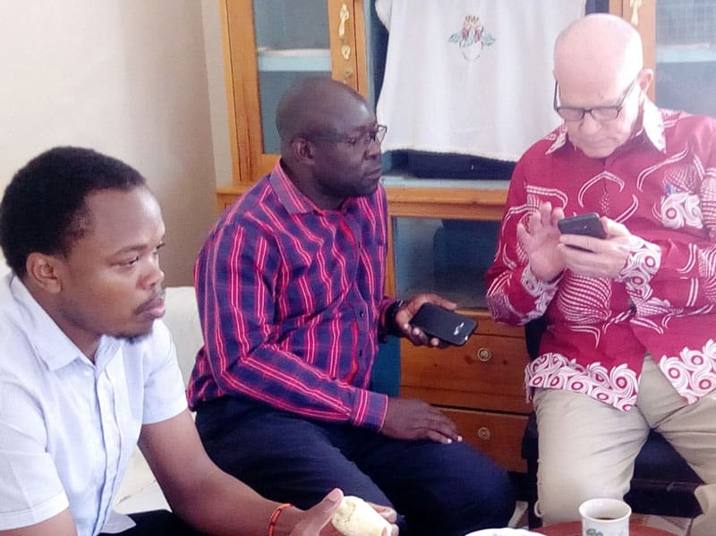 Maryknoll Father Joseph Healey (r.) explains voting on the SCCs Website to two members of the AMECEA Small Christian Communities Training Team in Nairobi, Kenya. (Courtesy of Joseph Healey/Kenya)