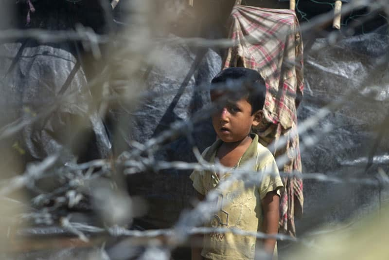 "Rohingya refugees gather near a fence in ""no man's land"" between Myanmar and Bangladesh as seen from Maungdaw, Rakhine State, on June 29. More than 700,000 Rohingya fled an army crackdown in August 2017 that the U.S. and U.N. have called ethnic cleansing. (Photo by Phyo Hein Kyaw/AFP via UCAN)"