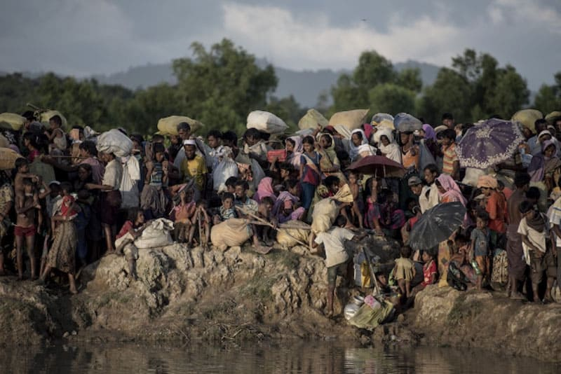 Rohingya refugees fleeing Myanmar arrive at the Naf River on the Bangladesh border on Oct. 10, 2017. In a final report released on Sept. 18, a U.N. probe says six members of Myanmar's military including chief Min Aung Hlaing should be investigated for genocide. (Photo by Fred Dufour/AFP via UCAN)